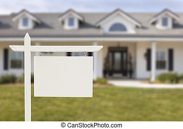 Signo de bienes raíces en blanco frente a la nueva casa