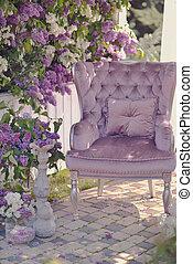 Silla y arbusto de lilas en flor