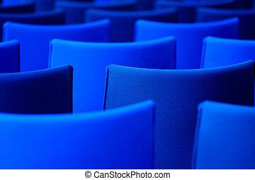 Sillas azules en la sala de conferencias.