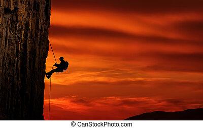 Silueta de escalador sobre una hermosa puesta de sol