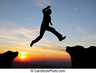 Silueta de excursionista saltando sobre las montañas al atardecer