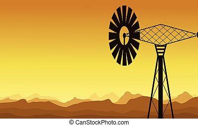 Silueta de molino de viento al amanecer