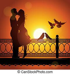 Silueta de pareja enamorada besándose al atardecer