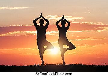 Silueta de pareja haciendo yoga