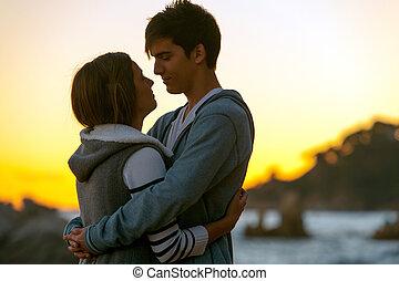Silueta de pareja romántica al atardecer.