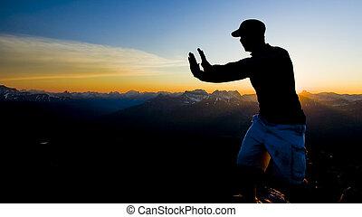 Silueta de persona en la cima de la montaña