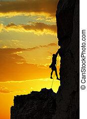Silueta de un escalador sobre una hermosa puesta de sol