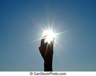 Silueta de una mano femenina, el cielo azul y el sol brillante 2