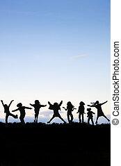 Silueta del grupo de niños saltando en el aire contra el cielo soleado