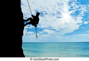 Silueta escaladora escalando una montaña