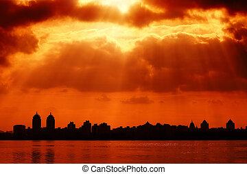 Silueta y cielo rojo con rayos solares