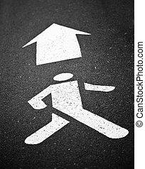 Simbolo peatonal blanco pintado sobre asfalto negro con flechas si