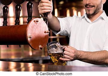 Sirviendo cerveza. Una imagen de barman sonriente sirviendo cerveza a la taza