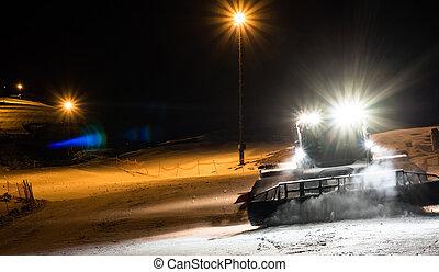 Snowcat preparando una pendiente por la noche