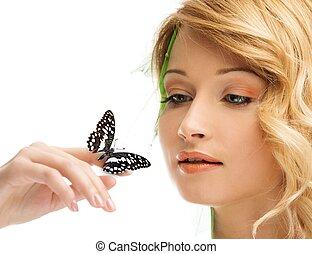 Soñando con una joven vestida de primavera con mariposa en la mano