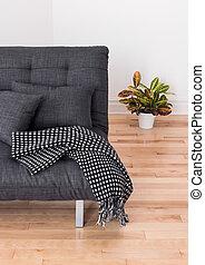 sofá gris y planta brillante en la sala de estar