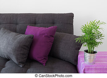 Sofa acogedora con almohadones y plantas verdes