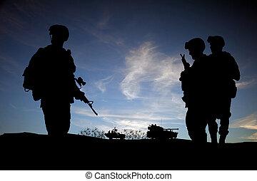 Soldados modernos del Medio Oriente silueta contra el cielo del atardecer con vehículos de fondo