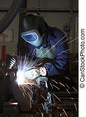 soldar una parte de metal en un ambiente industrial