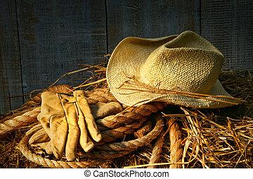 Sombrero de paja con guantes en un fardo de heno