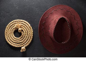 Sombrero de vaquero y lazo en el fondo negro