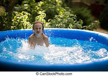 Sonriendo adorable niña de siete años jugando y divirtiéndose en piscina inflable