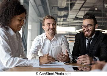 Sonriendo colegas diversos diversos divirtiéndose en la reunión de negocios en la oficina