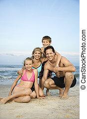 Sonriendo familia feliz en la playa.