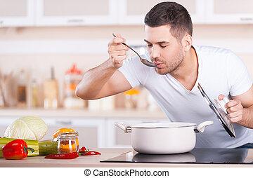 Sopa de sabor. Un joven apuesto que degusta sopa de la sartén mientras está en la cocina