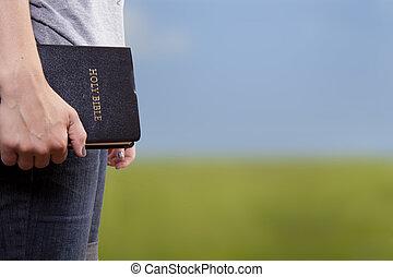 Sosteniendo la Biblia en un campo