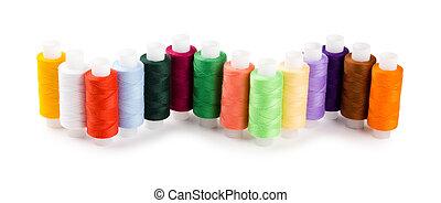 Spools hilos multicolores ubicaron una onda aislada en un fondo blanco