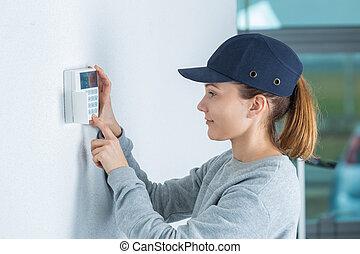 Técnica joven instalando sistema de seguridad