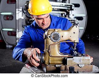 Técnico arreglando máquina de coser industrial