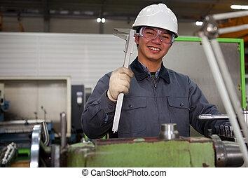 Técnico asiático en el taller de herramientas