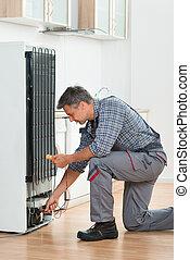 Técnico chequeando refrigerador con multimetro en casa