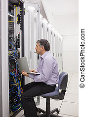 Técnico comprobando el servidor con su portátil