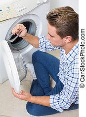 Técnico reparando una lavadora