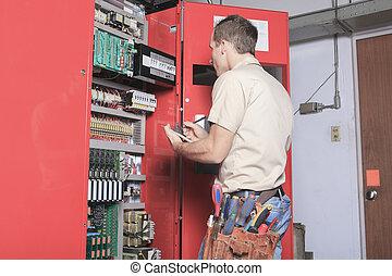 Técnicos maquinistas en el trabajo ajustando ascensor con llave inglesa
