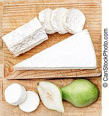 Tabla de queso con diferentes quesos, peras y uvas en fondo blanco de madera. La mejor vista. Copia espacio