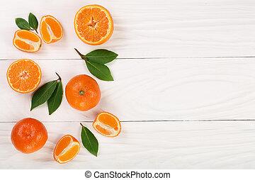 Tangerine con hojas de fondo blanco de madera con espacio de copia para su texto. Planta plana, vista superior. Composición de frutas