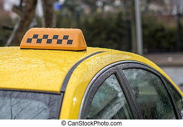 Taxi amarillo en la lluvia esperando pasajeros