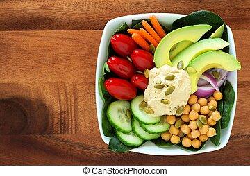 Tazón nutritivo para el almuerzo con aguacate, hummus y verduras mezcladas, vistas por encima en un tazón cuadrado de madera