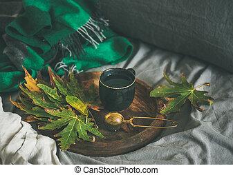 Taza negra de té con cola y hojas en bandeja