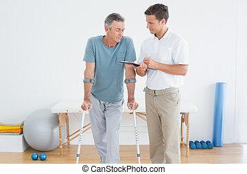 Terapeuta discutiendo informes con un paciente discapacitado