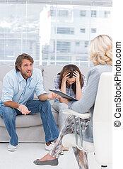 Terapeuta escuchando a la pareja sentarse en el sofá