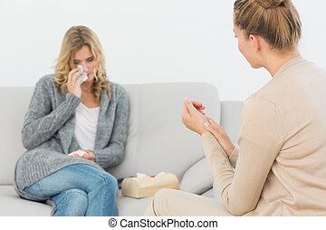 Terapeuta escuchando al paciente llorando en el sofá