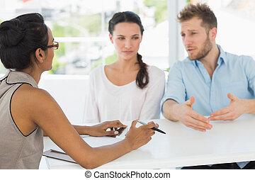 Terapeuta hablando con una pareja sentada en el escritorio