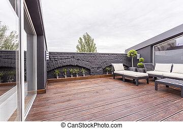 terraza oscura con muebles de jardín