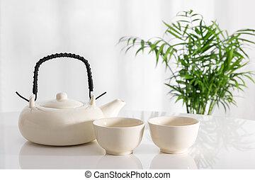 Tetera cerámica y tazas sobre la mesa