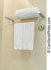 Toalla blanca limpia en una percha preparada en el baño.
